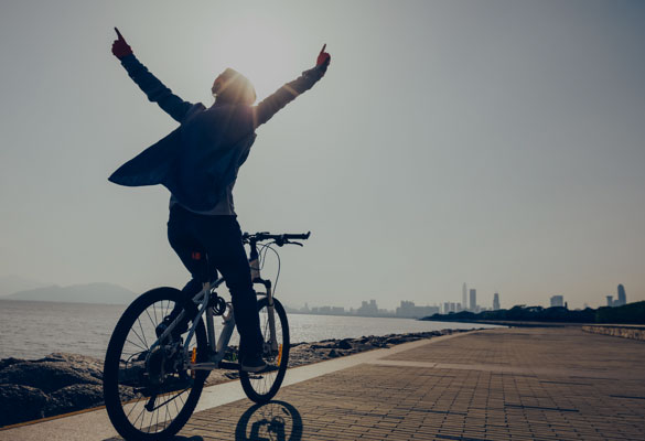 Person riding a bike happily after getting loan approved in minutes from Advance America