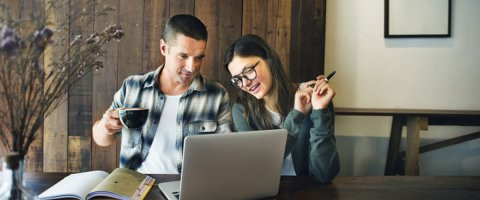 Couple look at laptop on how to get an unsecured line of credit online