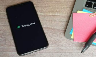 Phone showing Trustpilot icon with laptop