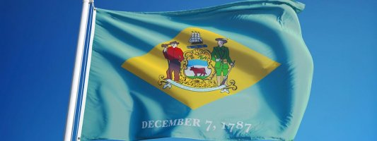 Delaware flag with blue sky background