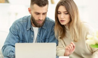Couple looking at computer for loan options for holiday debt